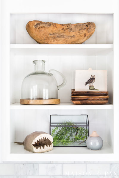 shelves styled with natural wood tones, greenery, and vintage art | Maison de Pax