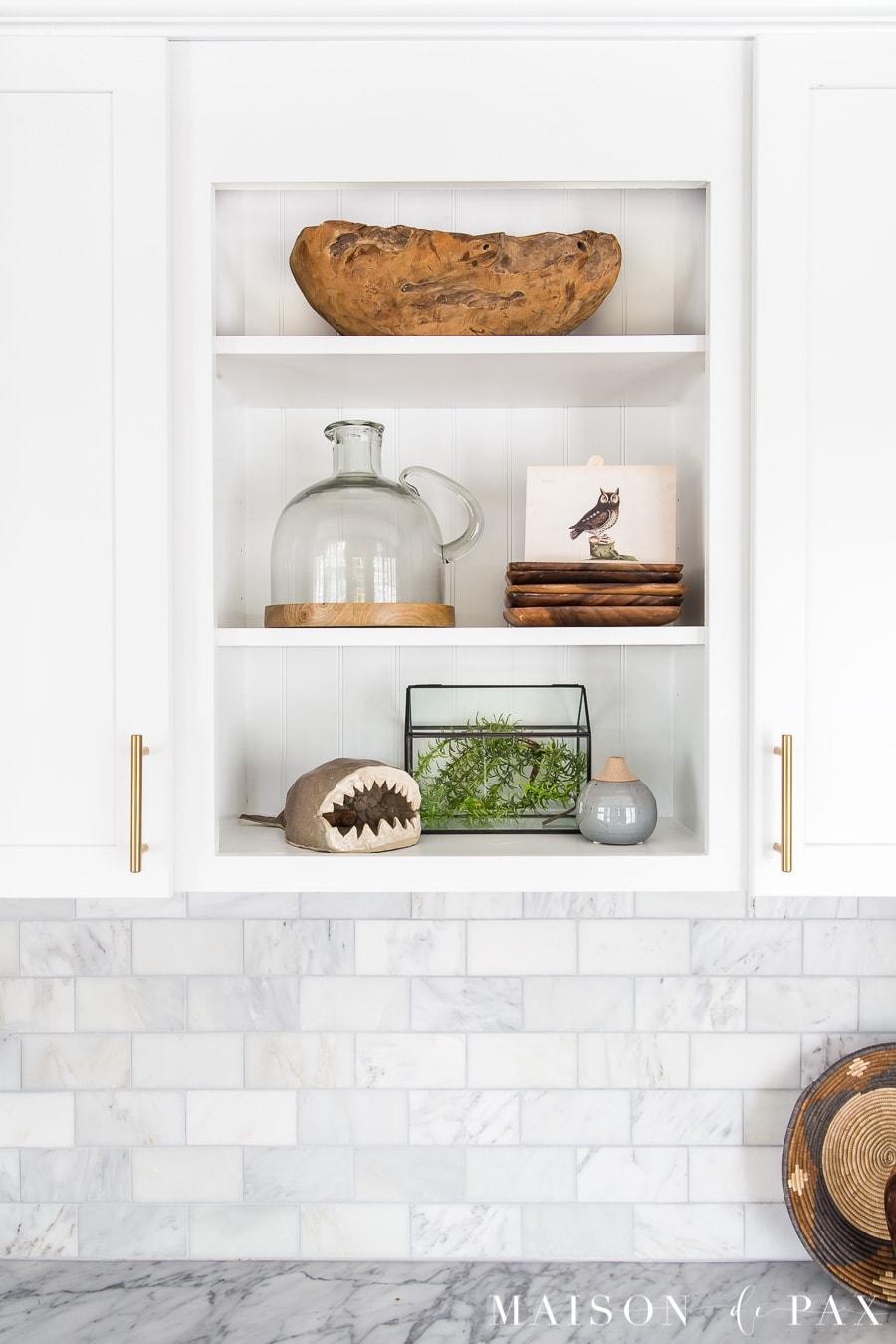 open shelves styled with wood bowl, glass terrarium, pottery, and vintage art | Maison de Pax