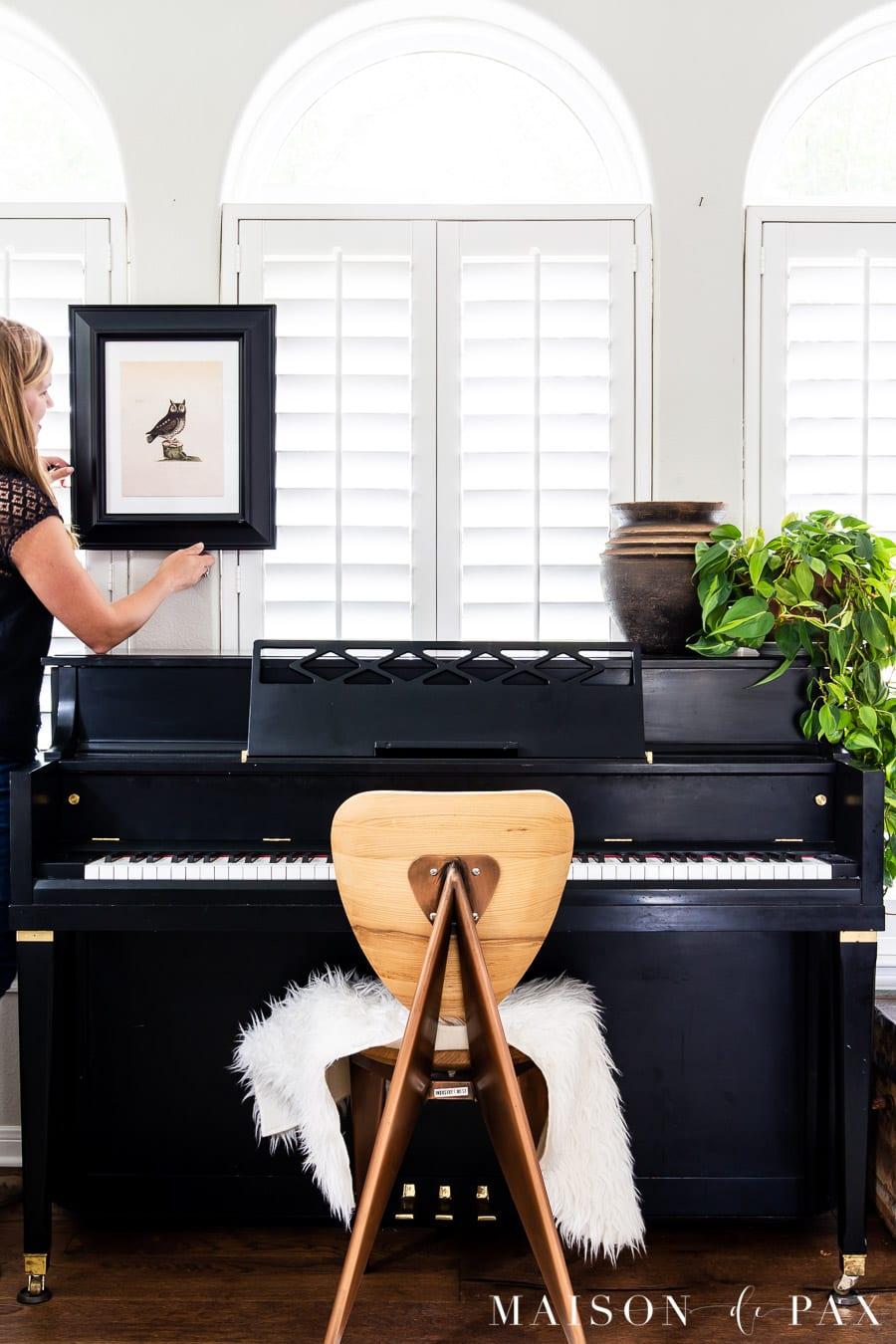 black piano with vintage art above | Maison de Pax