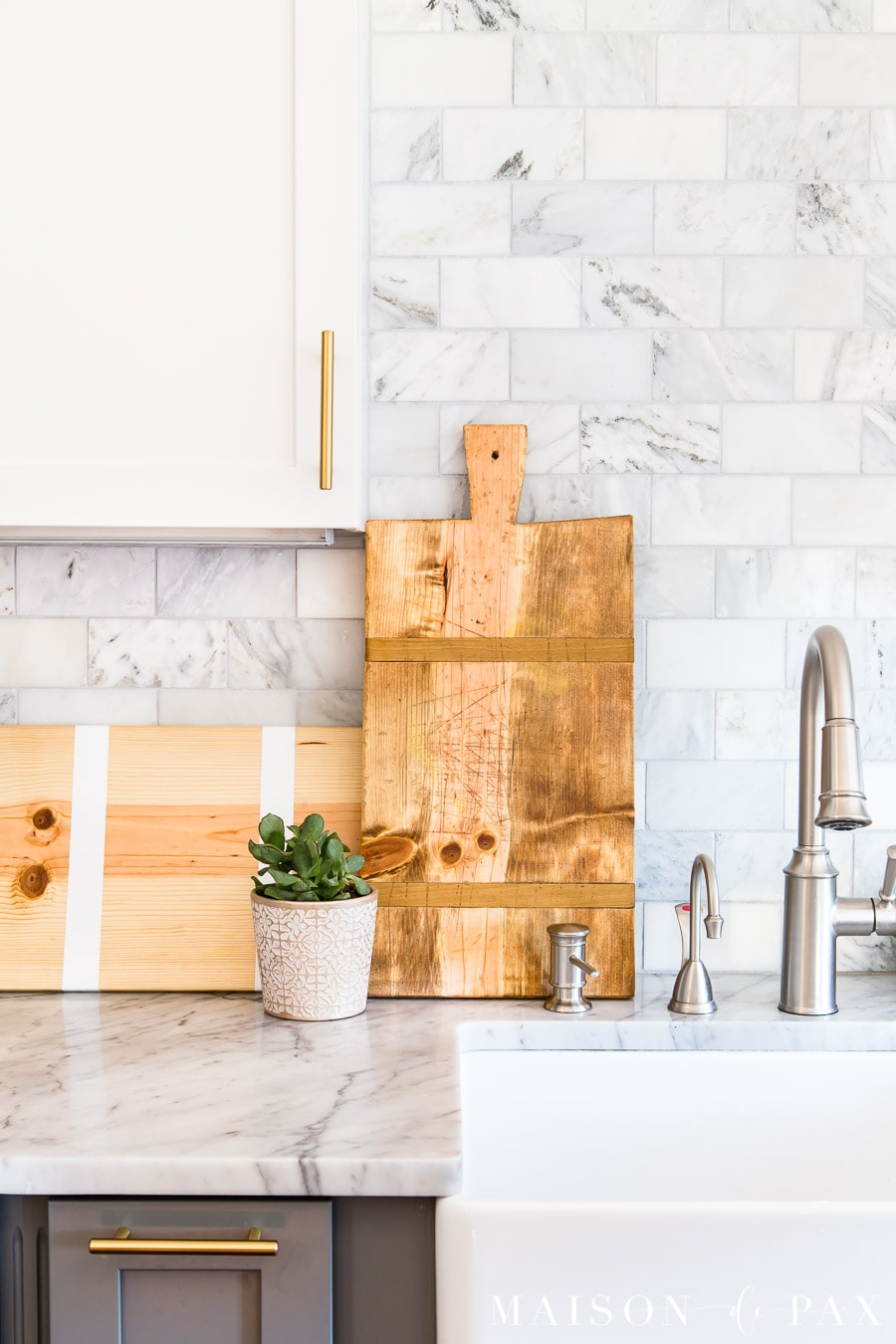gorgeous antique french breadboards on display in marble kitchen | Maison de Pax
