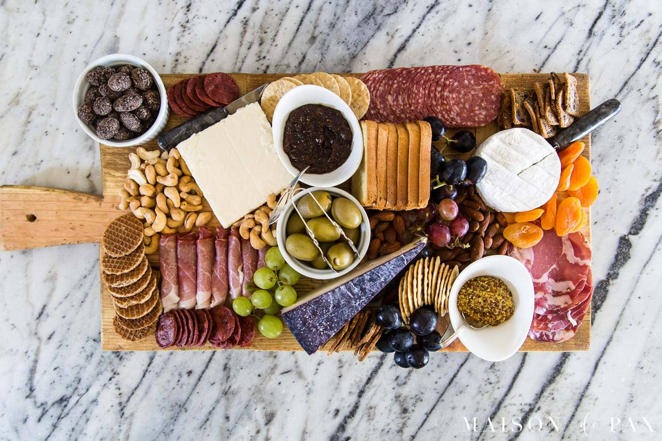 diy charcuterie board filled with cheeses, cured meats, dried and fresh fruits, and other treats | Maison de Pax