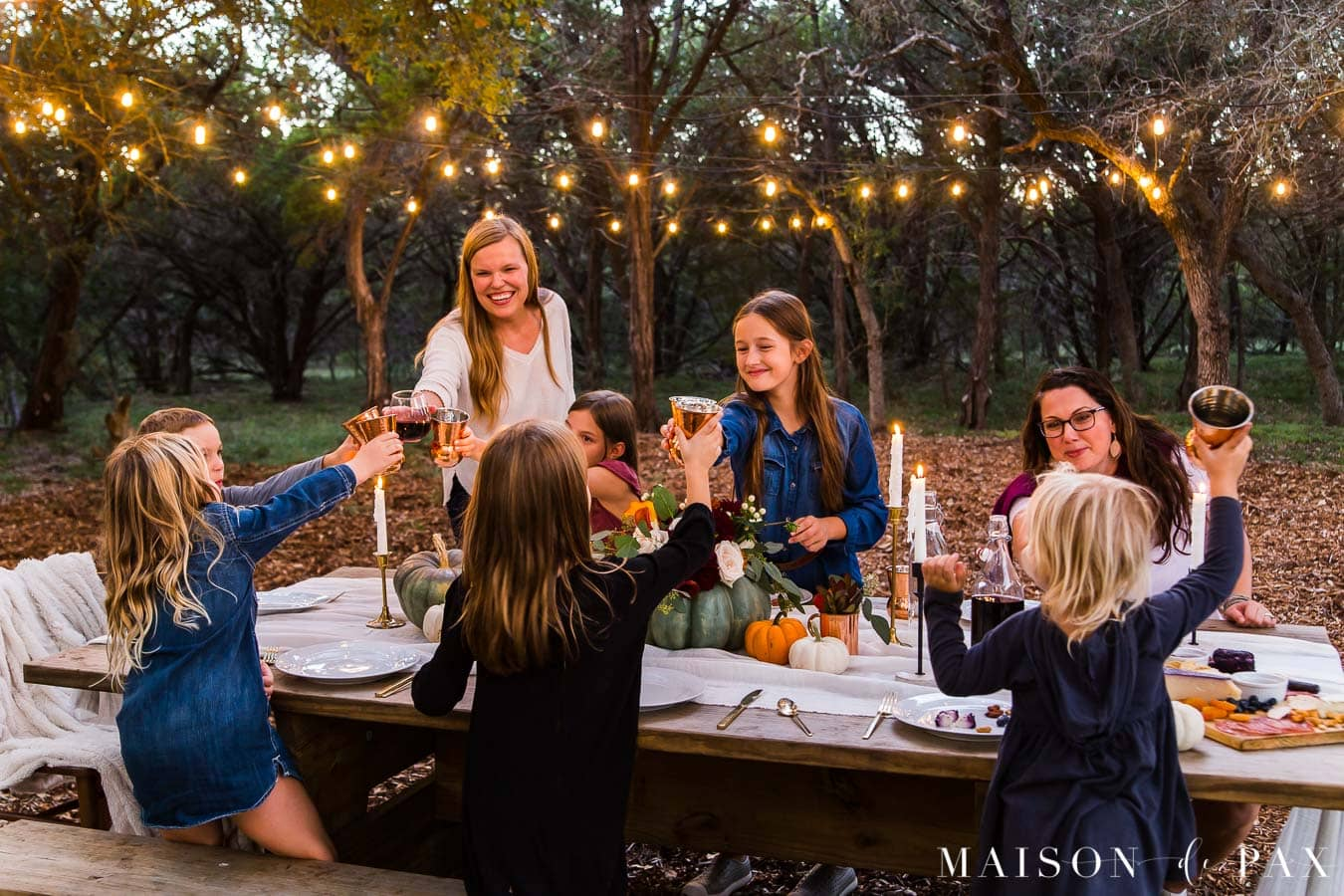 friendsgiving out in the woods with candles and string lights | Maison de Pax