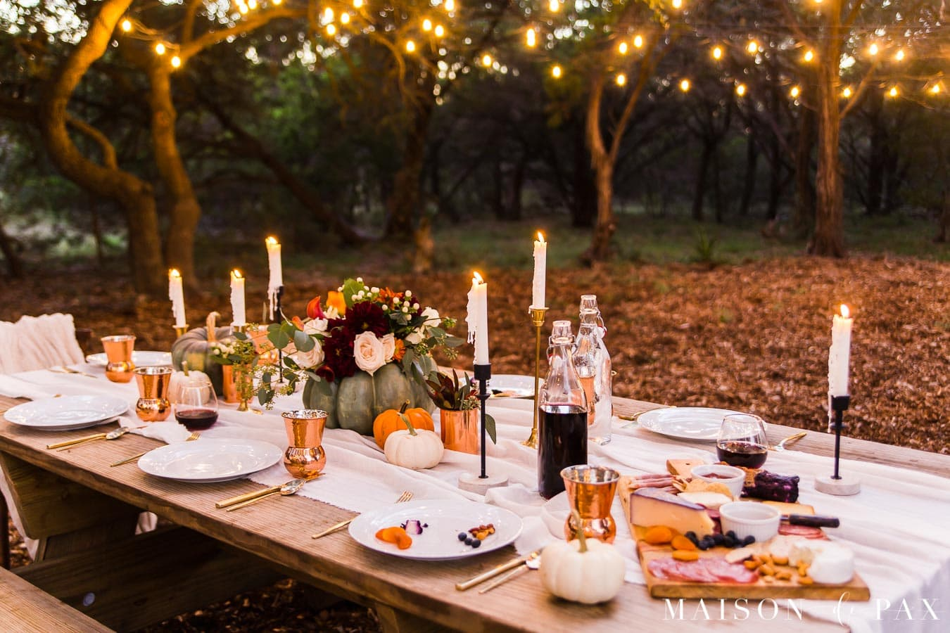 string lights over Thanksgiving table with pumpkins and candles | Maison de Pax