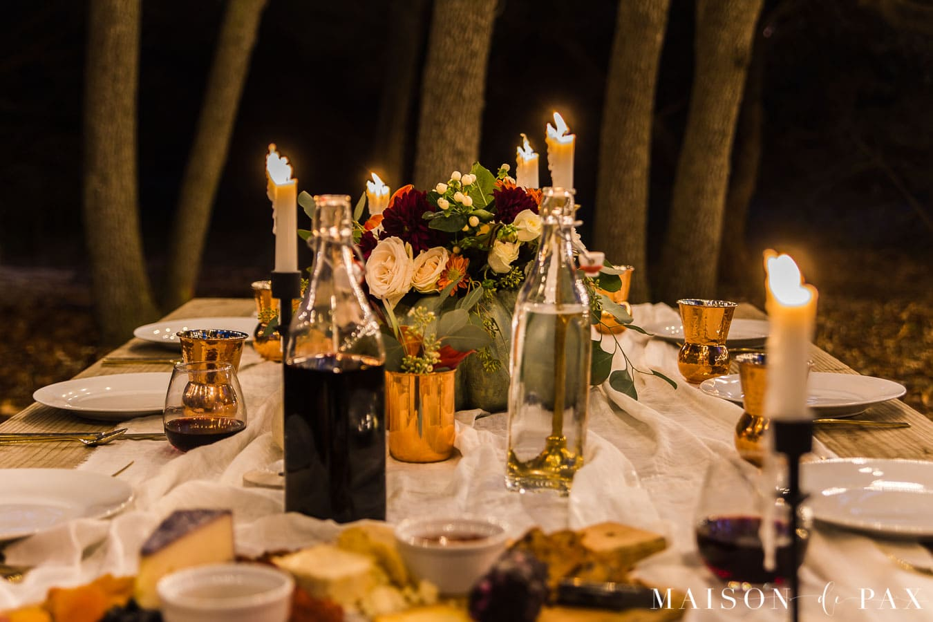 nighttime outdoor Thanksgiving table with taper candles | Maison de Pax