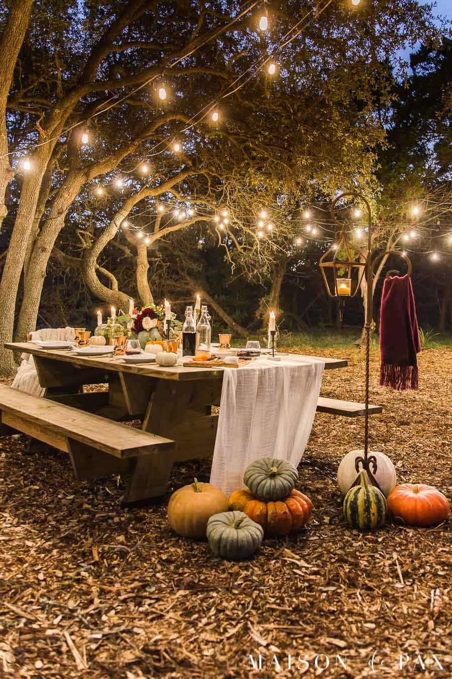 outdoor friendsgiving nighttime table with string lights | Maison de Pax