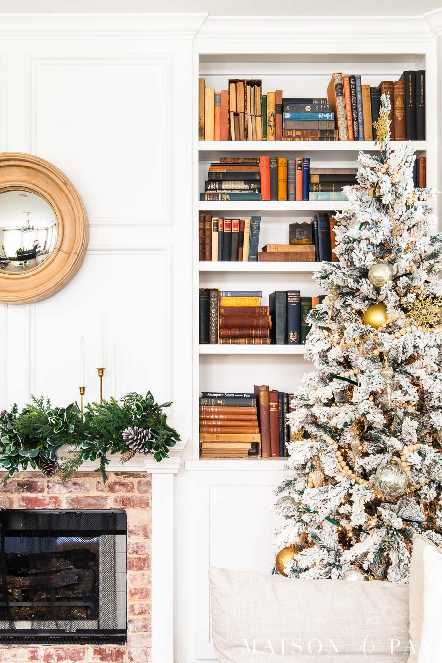 flocked tree with gold ornaments by fireplace | Maison de Pax
