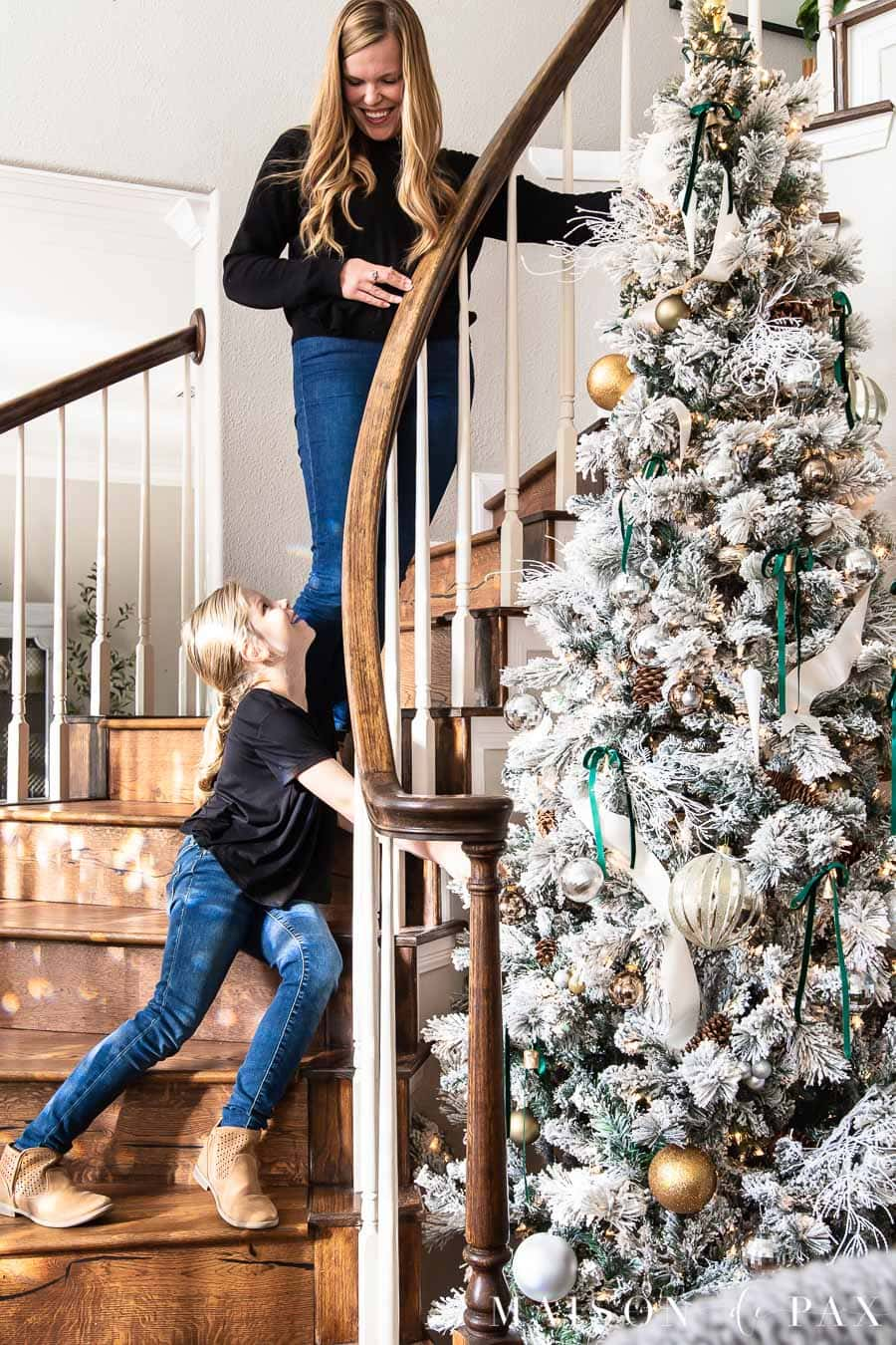 mother daughter decorating tall flocked Christmas tree | Maison de Pax
