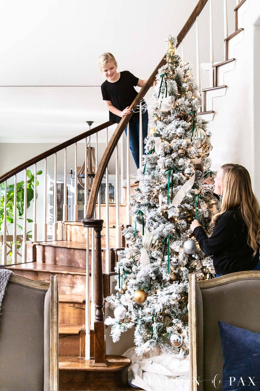 mother and daughter decorating large flocked Christmas tree in stairwell | Maison de Pax