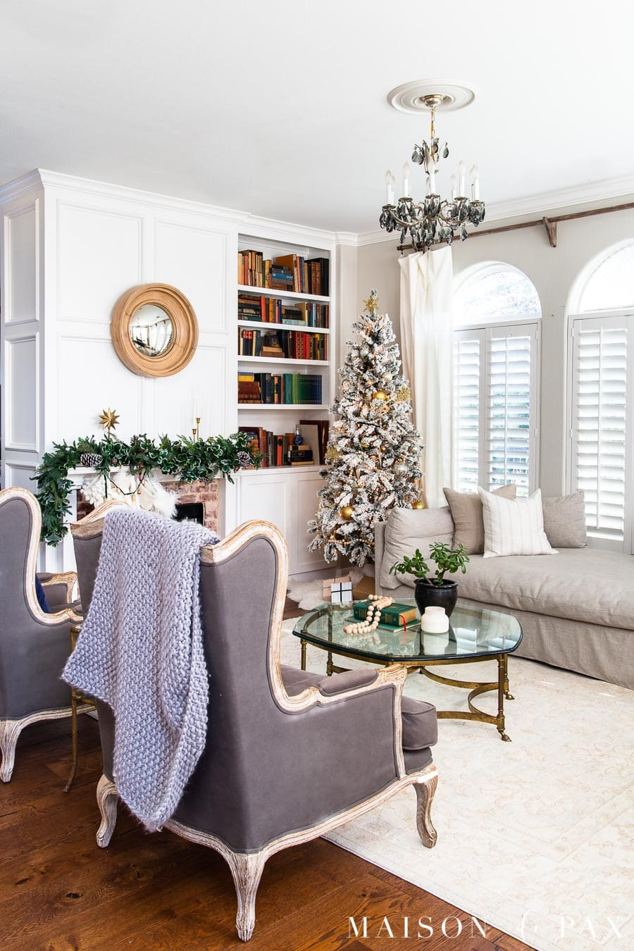 traditional living room with flocked christmas tree and green mantel garland | Maison de Pax