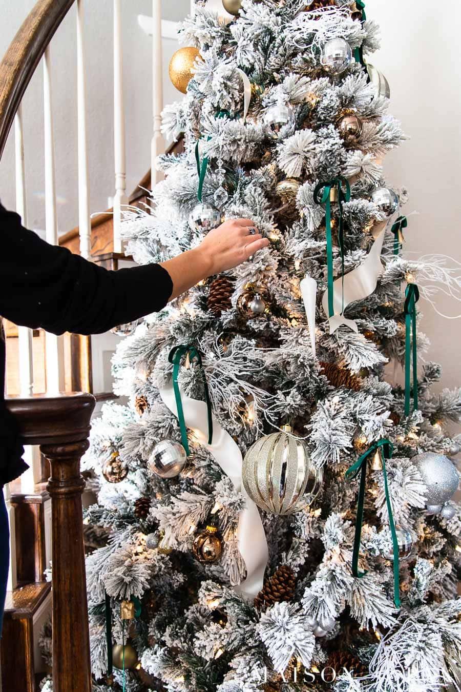 gold bells and dark green velvet ribbon on flocked Christmas tree | Maison de Pax