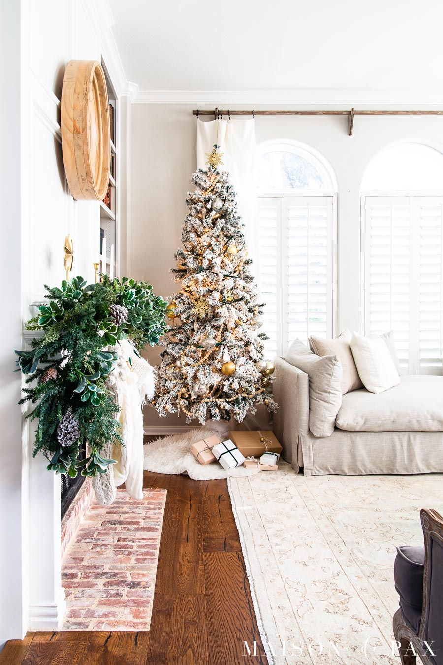 flocked tree tucked beside neutral sofa | Maison de Pax