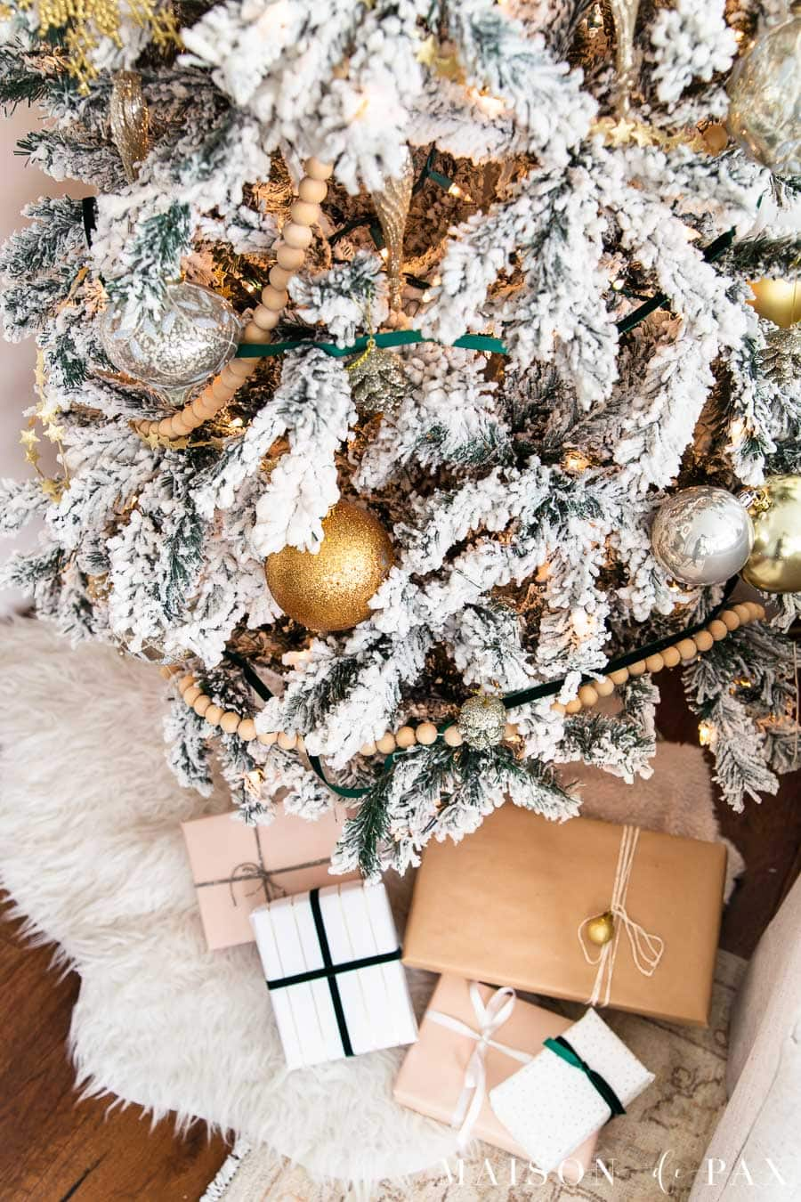 flocked tree with wood bead garland and green velvet ribbon | Maison de Pax