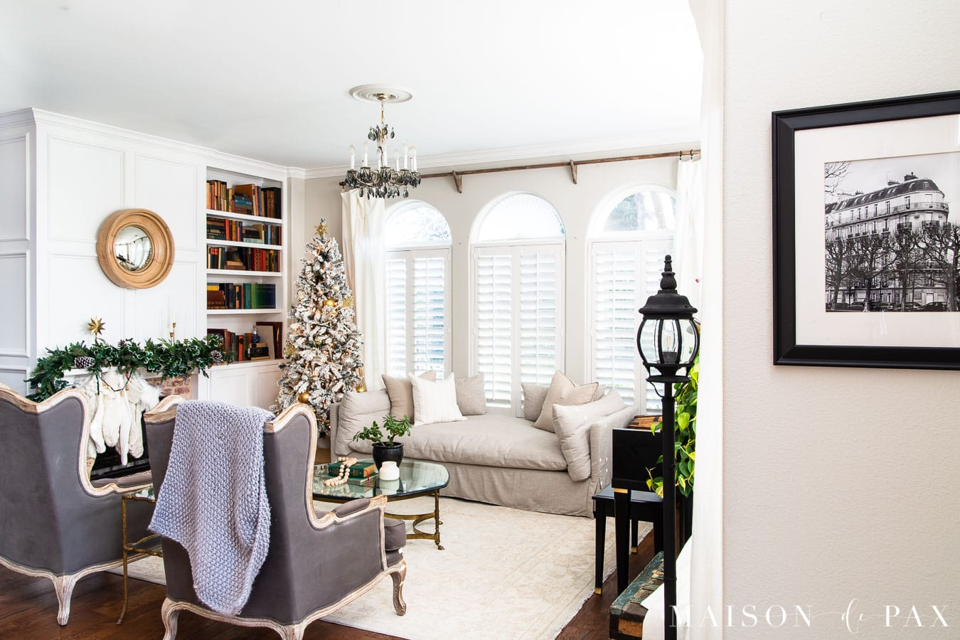 white living room with green garland above mantel and flocked tree | Maison de Pax