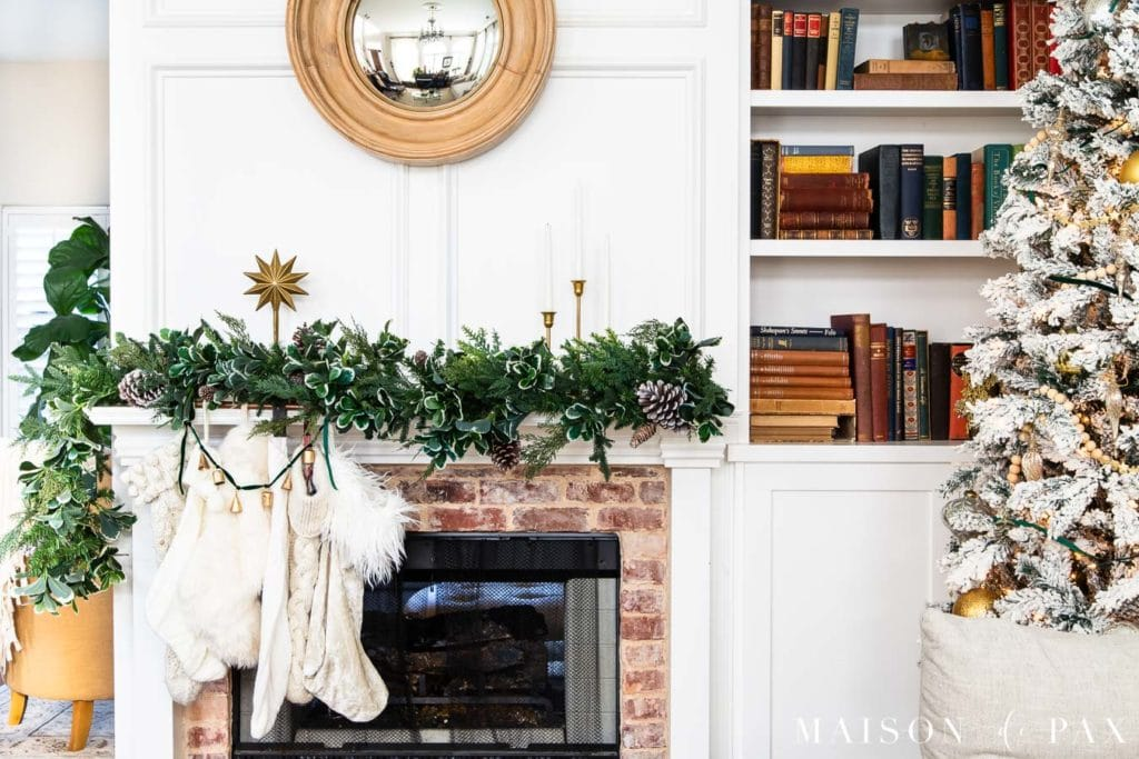 mantel with green garland, white stockings, and gold accents | Maison de Pax