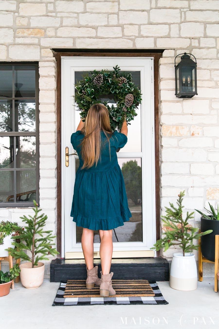 woman hanging wreath on storm door on farmhouse porch | Maison de Pax