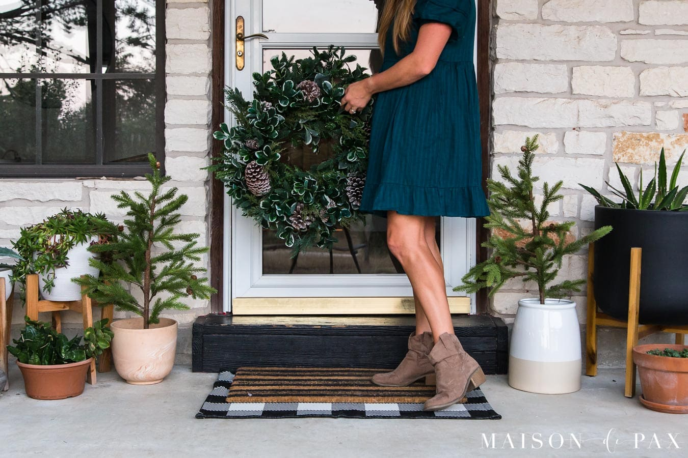 woman holding large mixed green wreath in front of door on little farmhouse porch | Maison de Pax