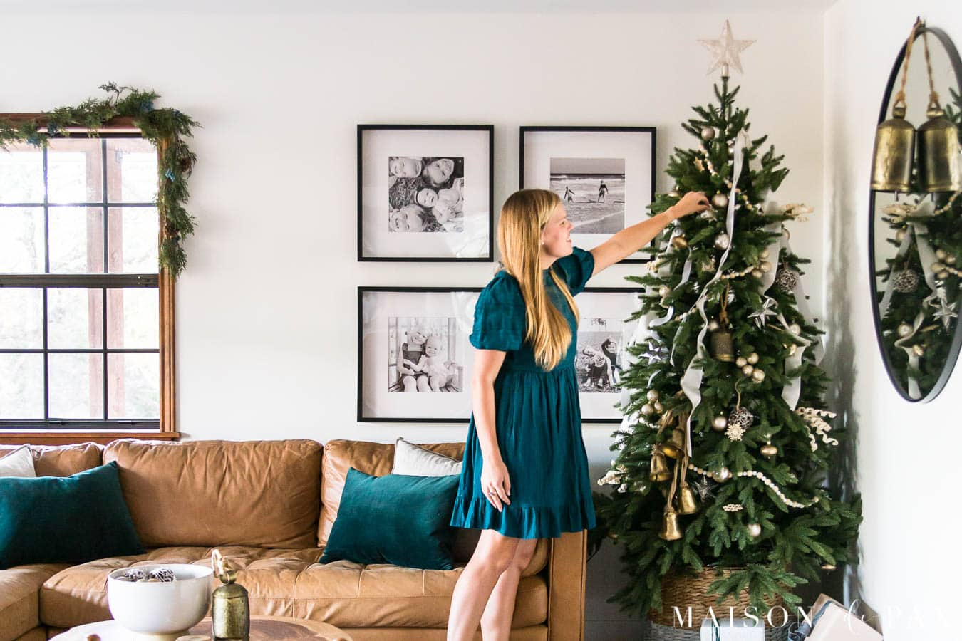 woman decorating green tree with gold and white decorations | Maison de Pax