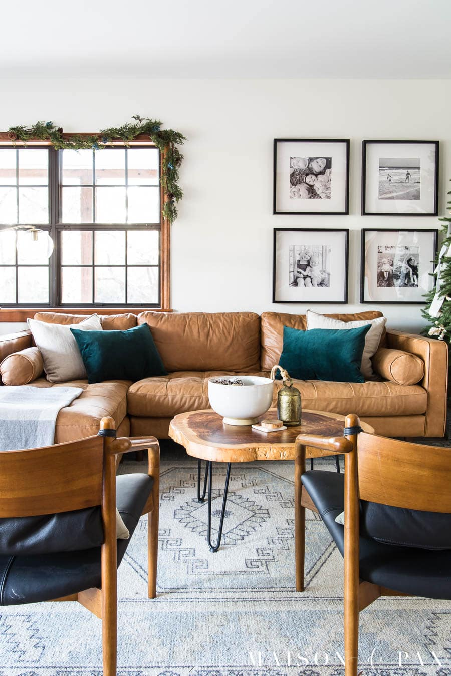 tan leather sofa with green velvet pillows and garland for holiday decorations | Maison de Pax