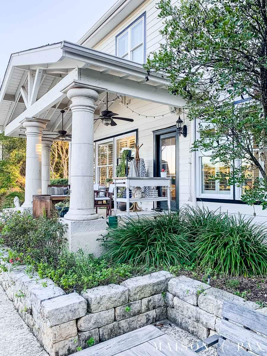stone garden border in back of white house with large porch and black trim | Maison de Pax