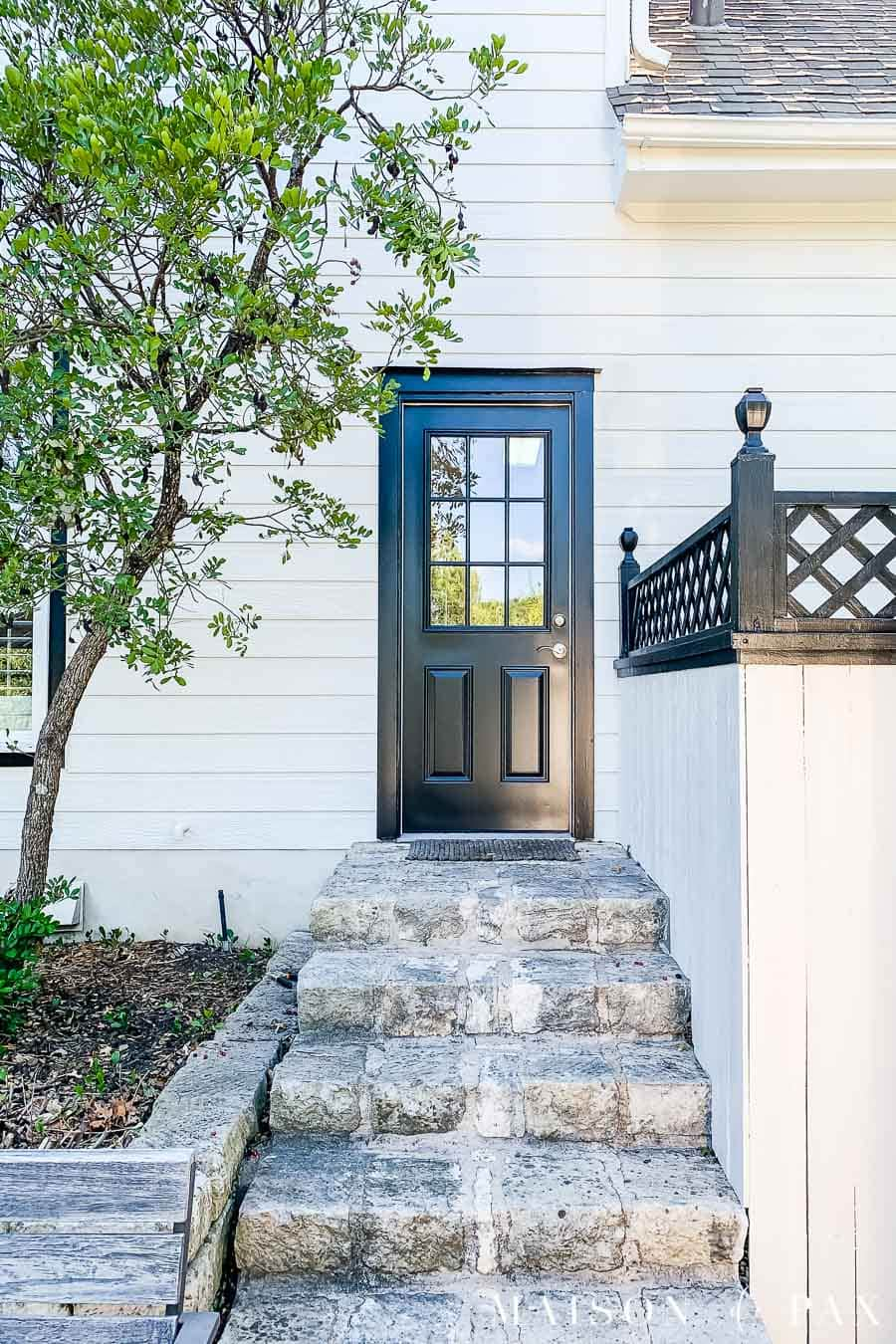 black door on house with white duck siding, white fence, and black lattice | Maison de Pax