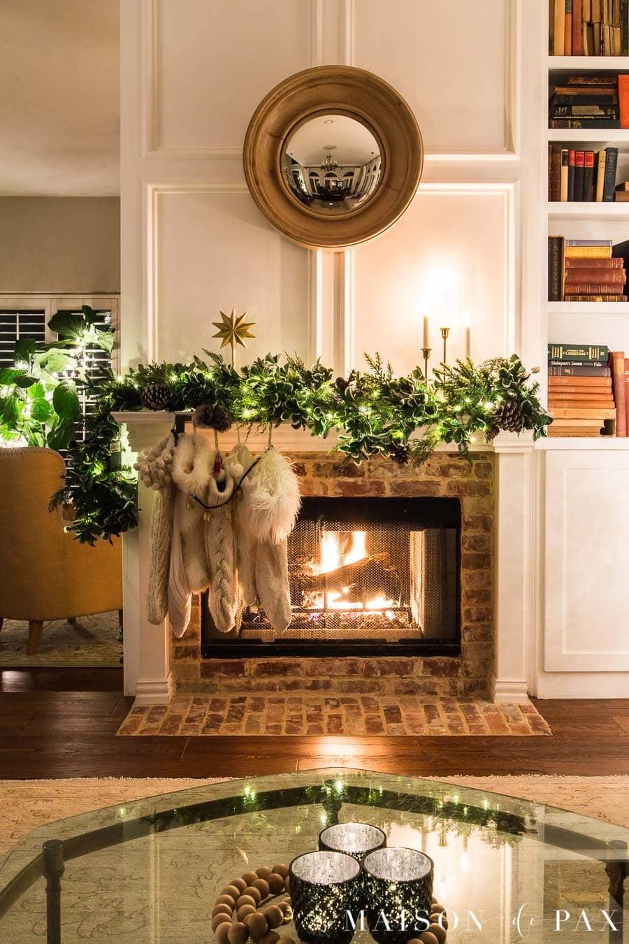 fireplace with asymmetrical garland, off white stockings, gold candles | Maison de Pax