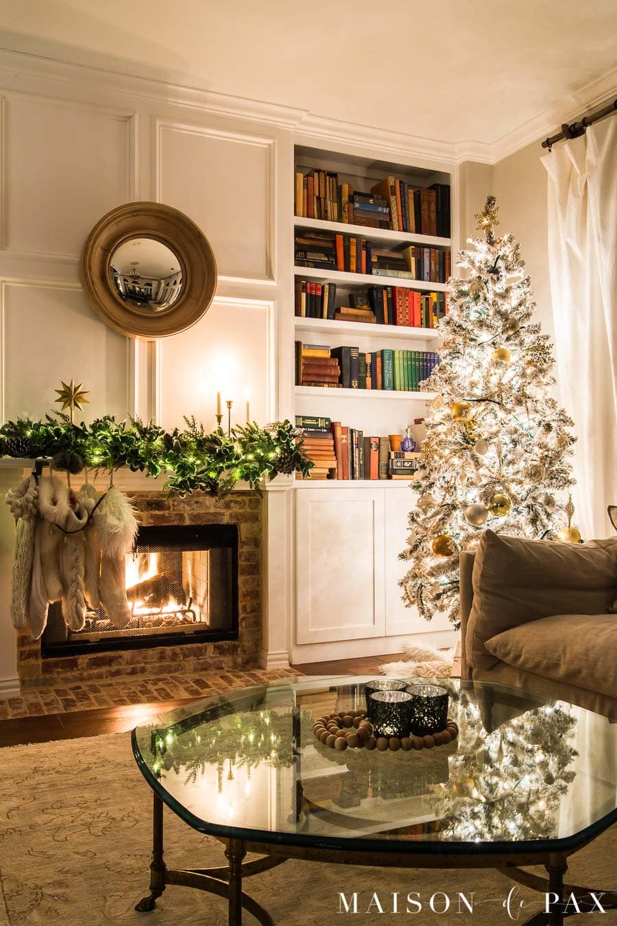 Flocked Christmas tree beside bookcase and fireplace | Maison de Pax