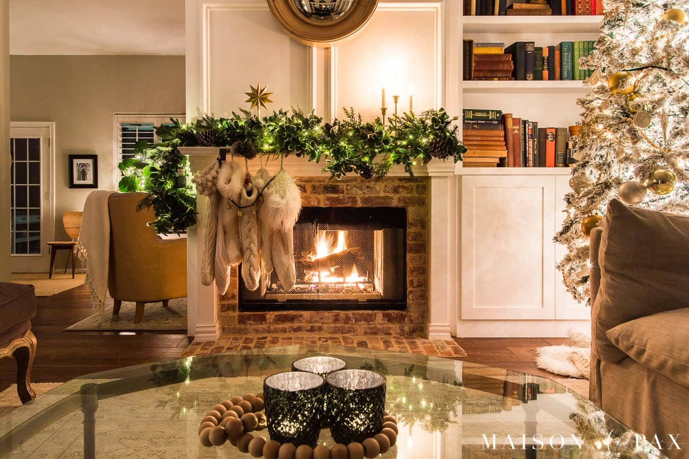 candles on the coffee table and a fire in the fireplace by the Christmas tree | Maison de Pax