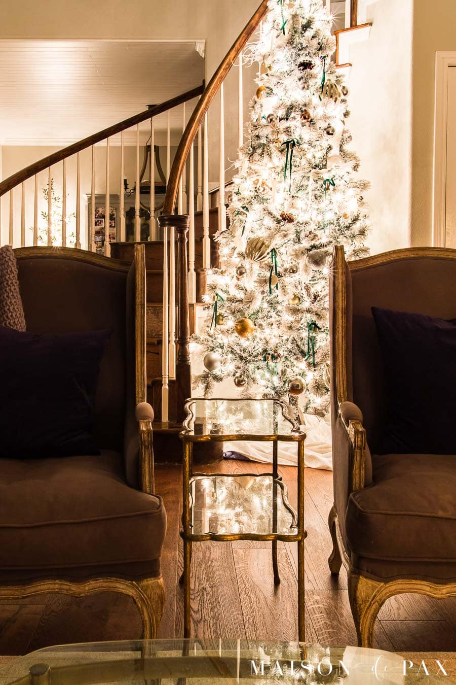 large flocked Christmas tree in curved stairway | Maison de Pax