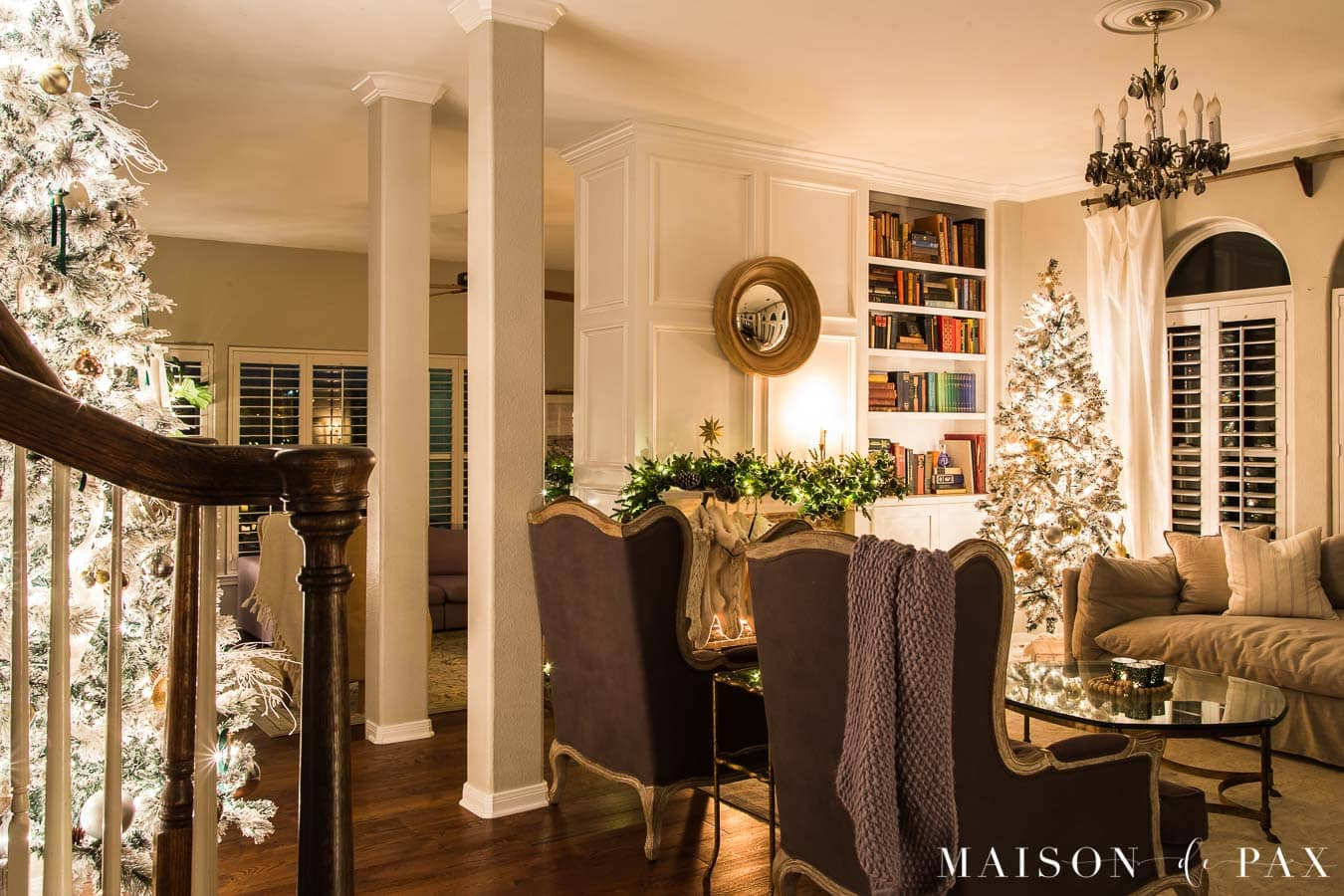 Living room with two Christmas trees and a fireplace decorated with garland | Maison de Pax