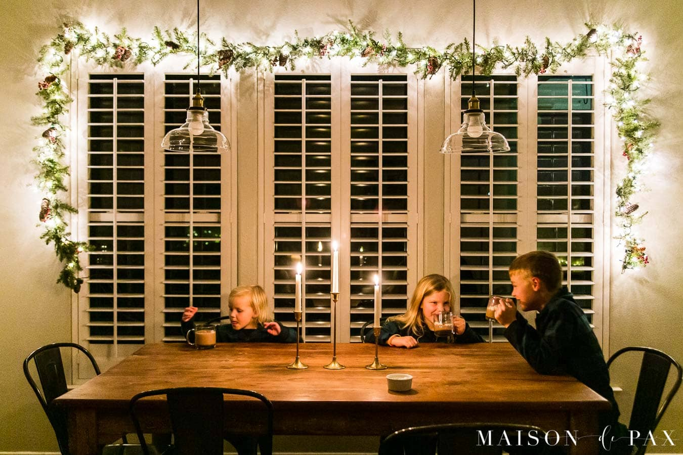 kids enjoying hot chocolate at the table by candlelight | Maison de Pax