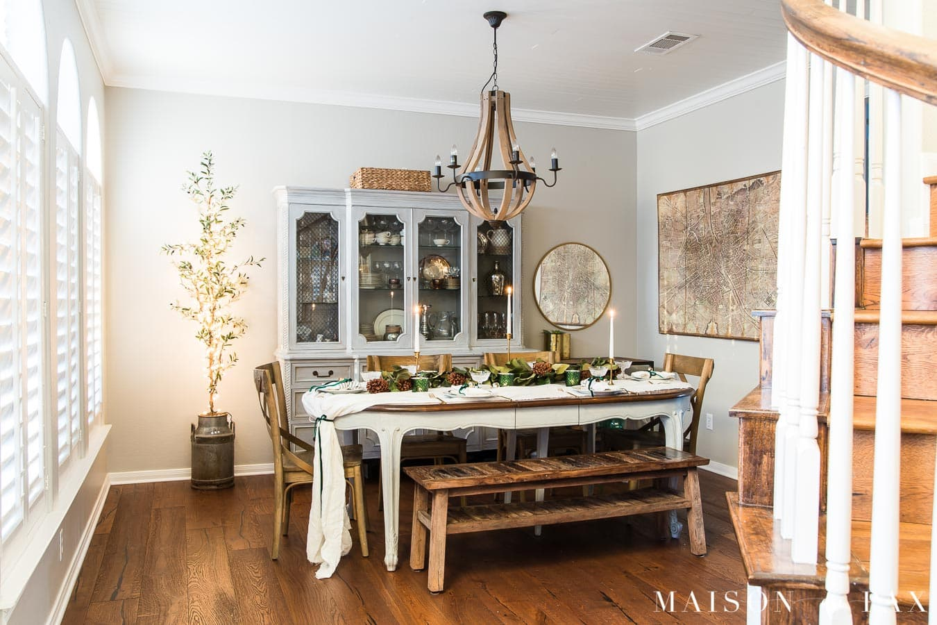 olive tree with Christmas lights beside dining table with holiday decorations | Maison de Pax