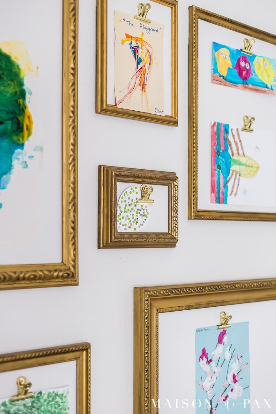 large gold clips hold children's artwork for display | Maison de Pax