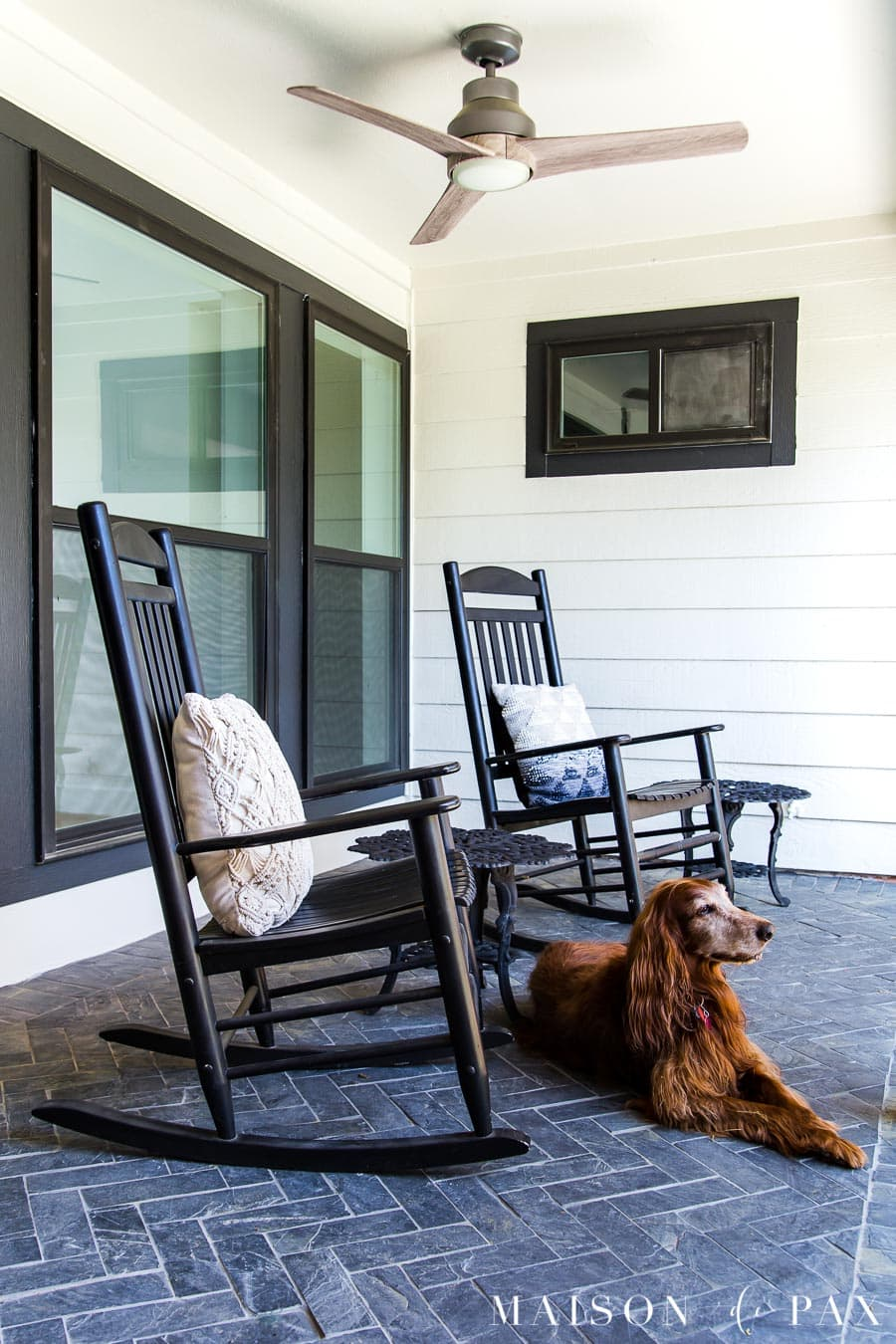 black and white porch with slate floors and outdoor ceiling fan