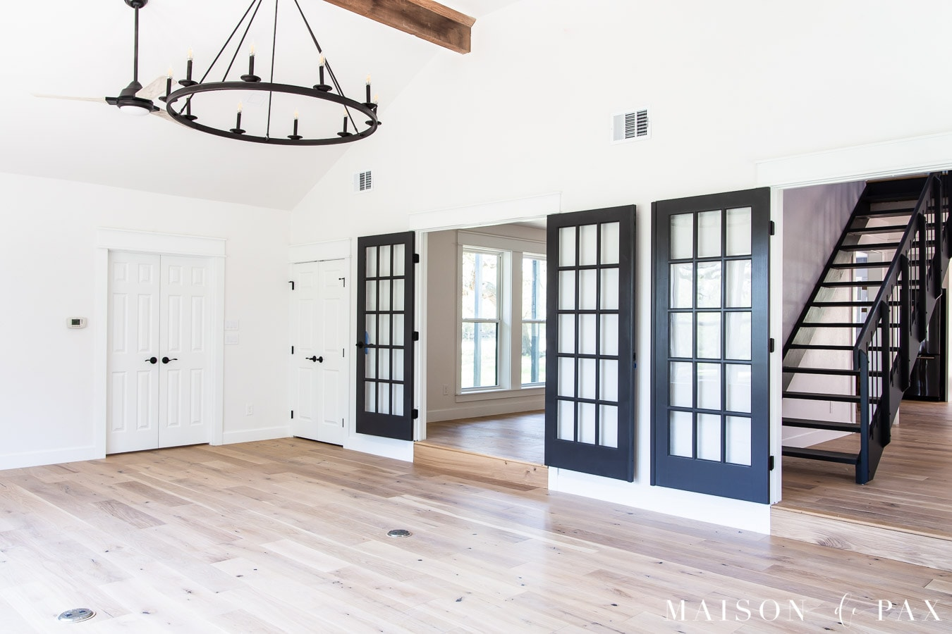 wide plank oak floors with ceiling beams and black fans