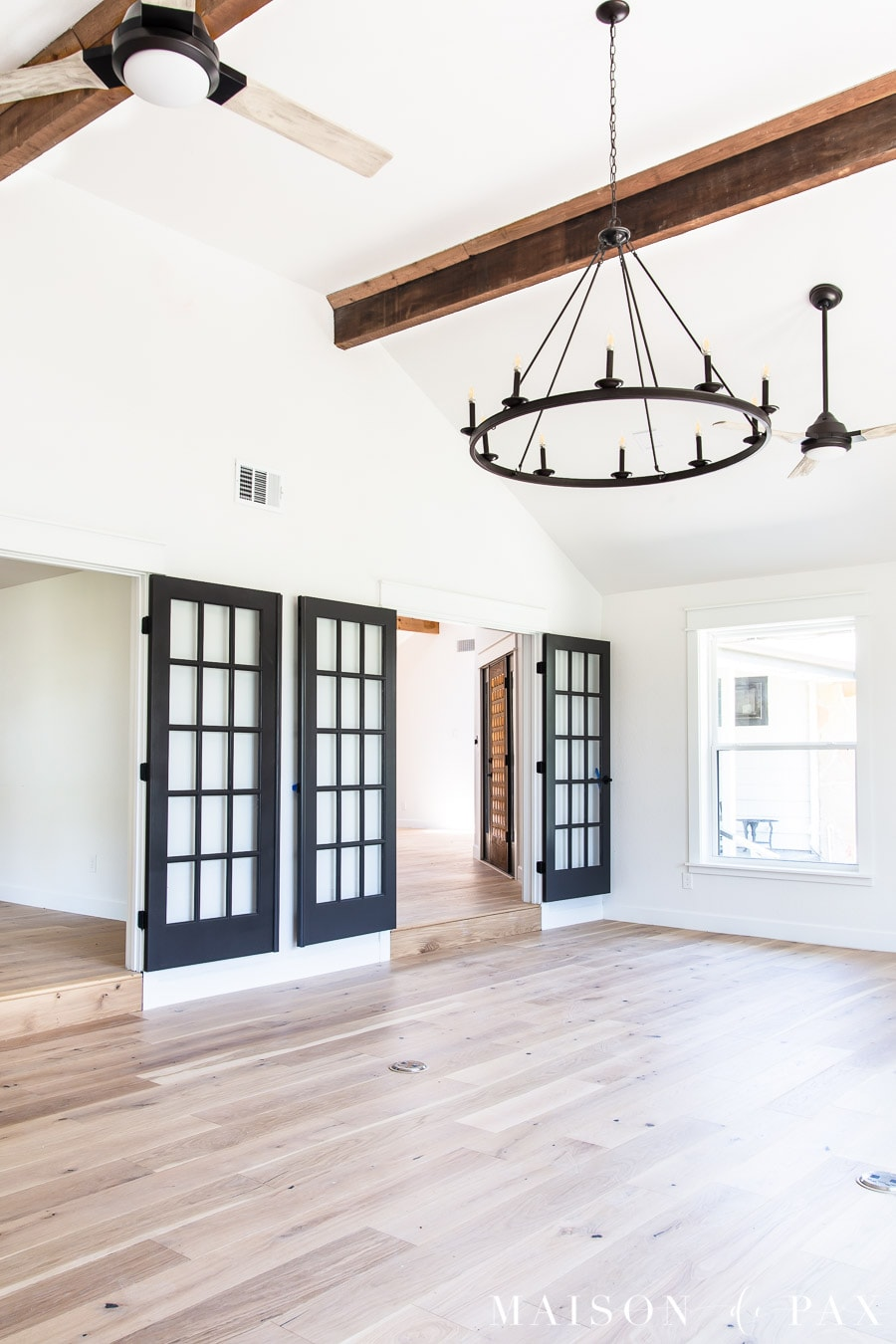 black french doors and black fans with whitewashed blades