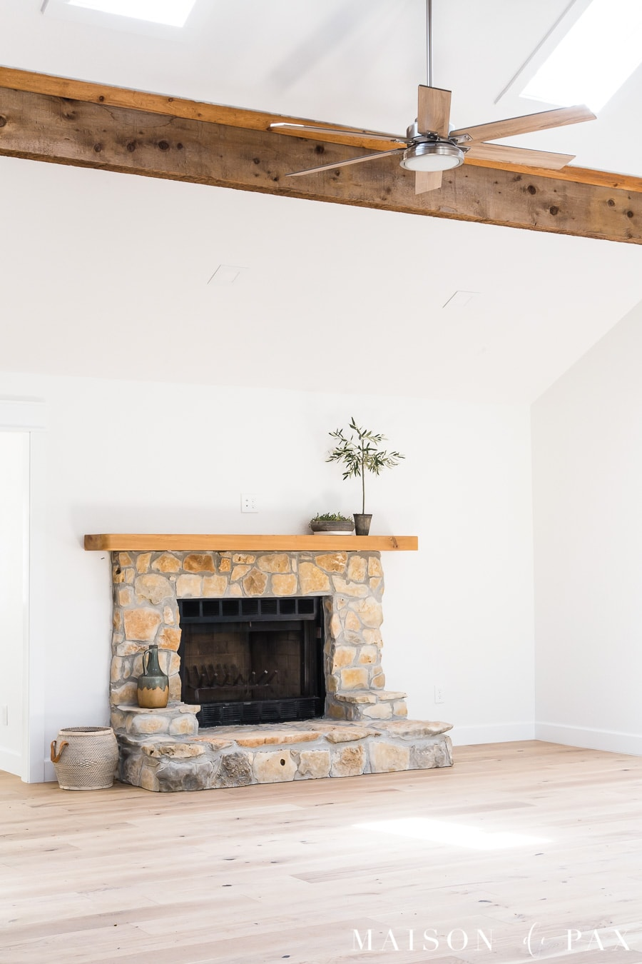 great room with ceiling fan and exposed beams