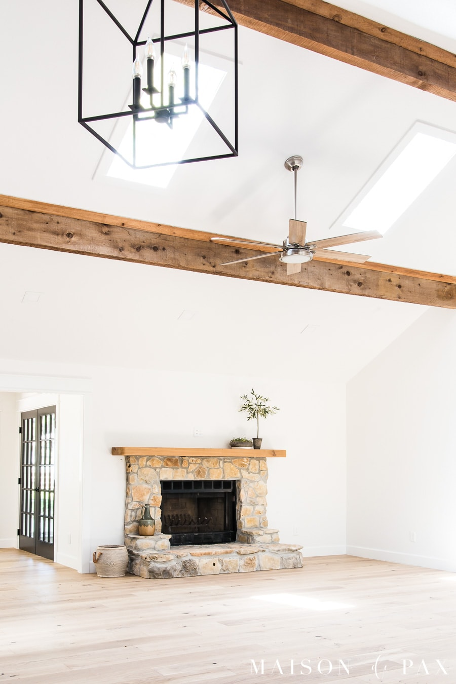 large living room with exposed beams, ceiling fan, and chandelier