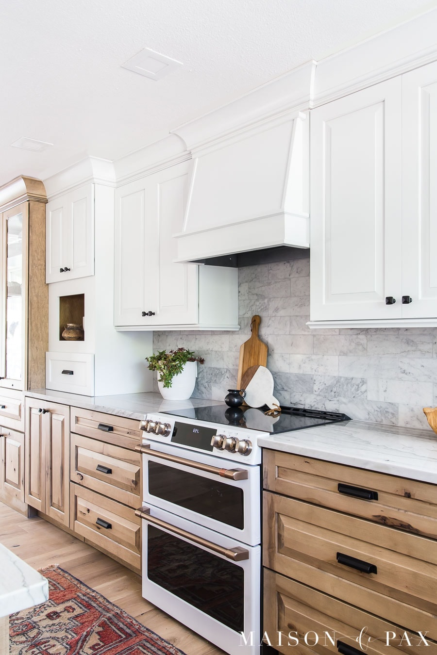 white cabinets and vent hood above range