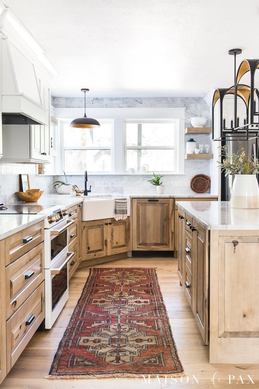 natural wood cabinets with marble backsplash