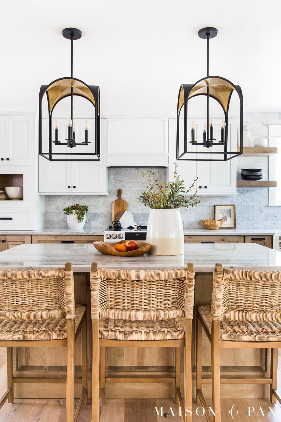 white and wood kitchen with black and gold lanterns over kitchen island