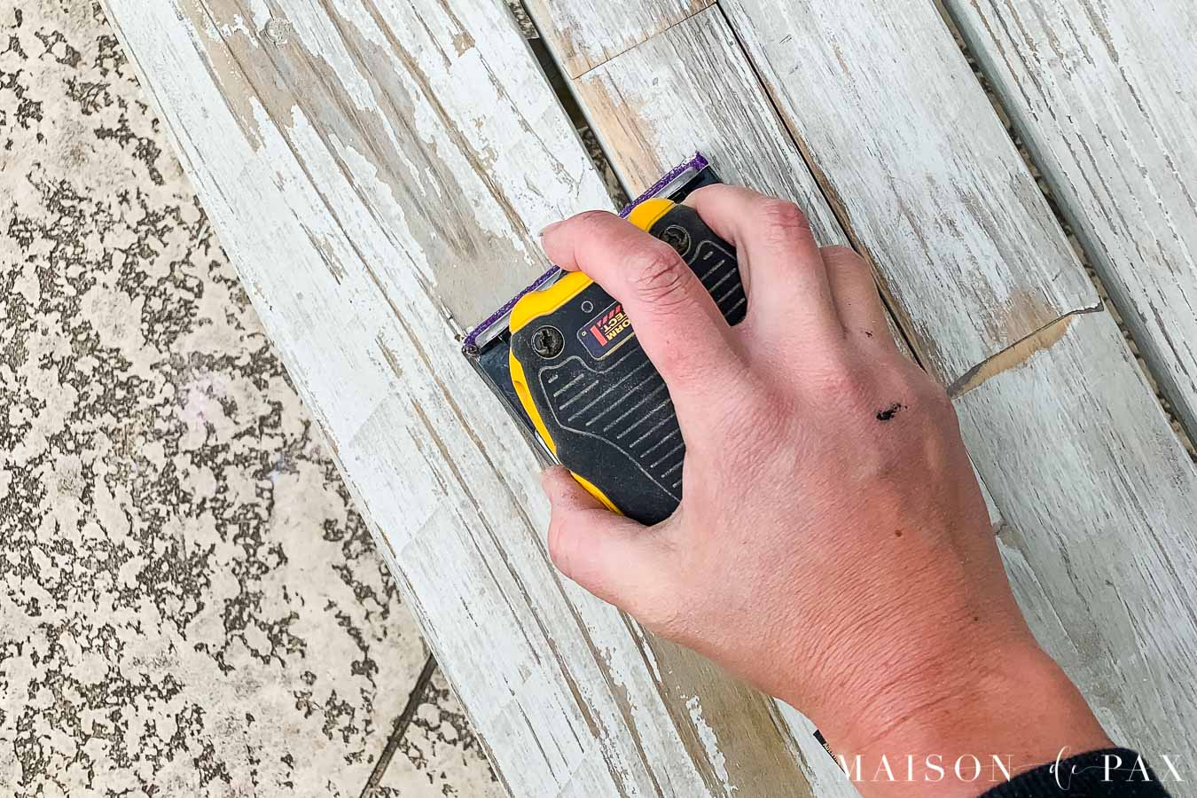 sanding chipping paint in preparation for painting outdoor furniture