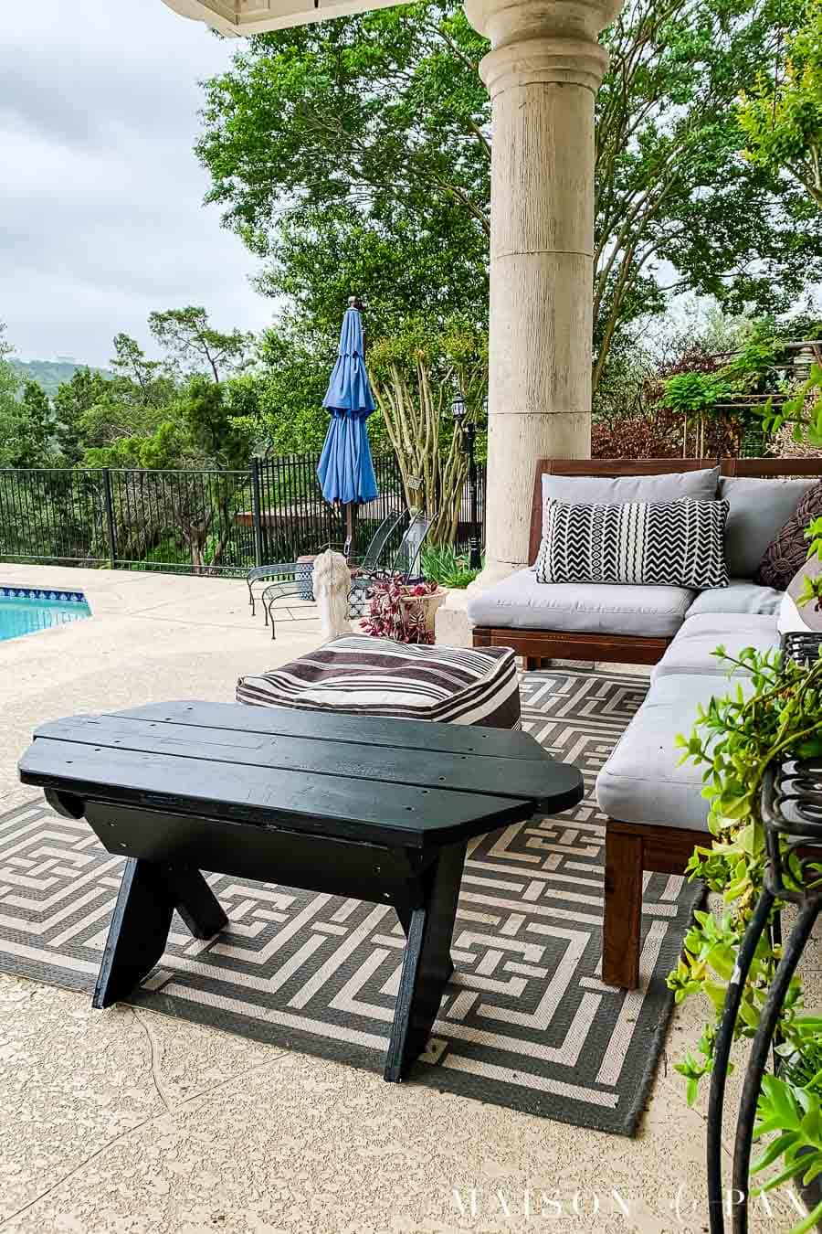 Black painted bench on patio