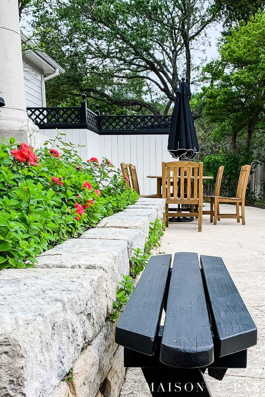 black painted bench outside on deck