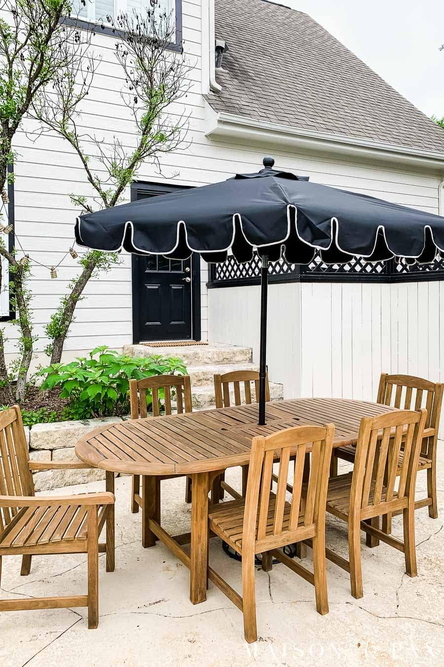 golden teak outdoor dining set with black umbrella