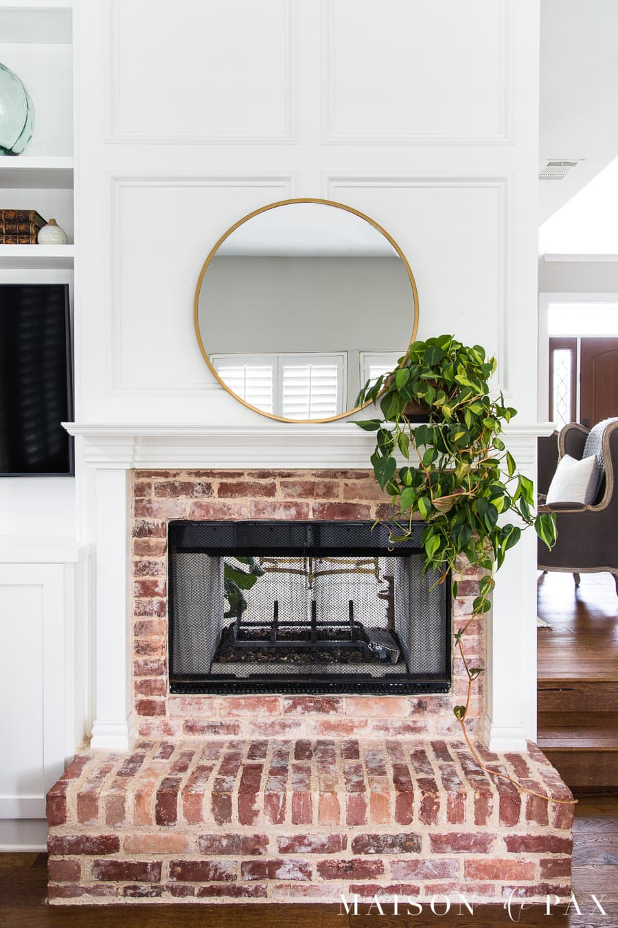 round brass mirror above mantel with trailing philodendron | Maison de Pax