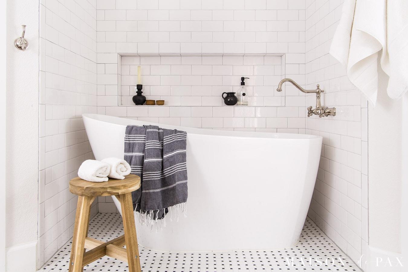white slipper tub with large tiled tub shelf