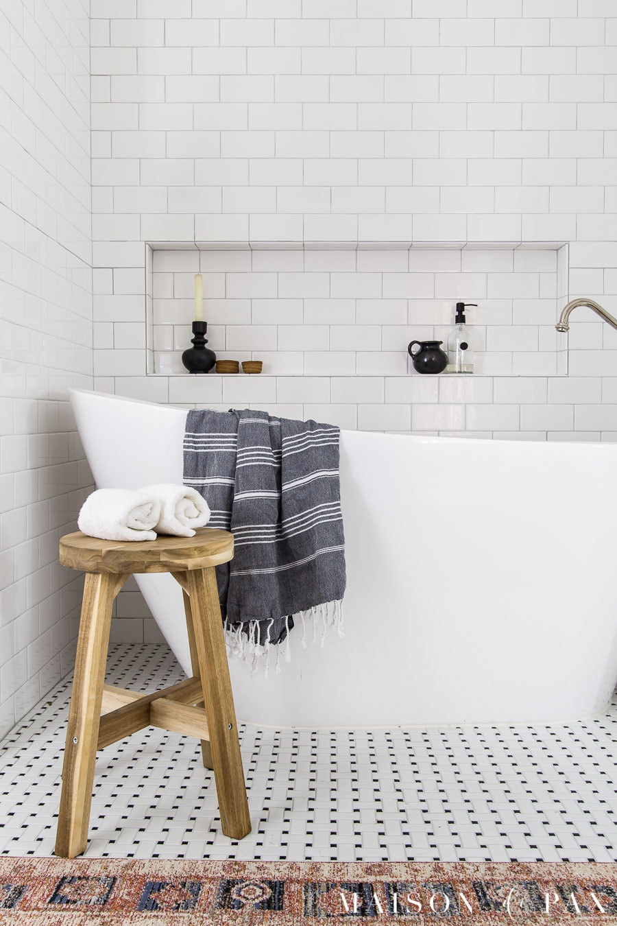 freestanding slipper tub with wood stool and turkish towel