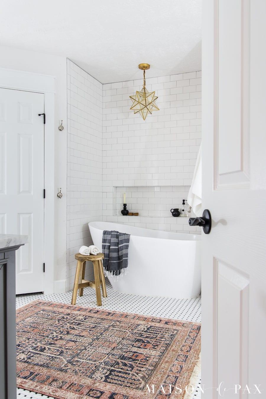 subway tile bathroom with black and white basketweave floor tile