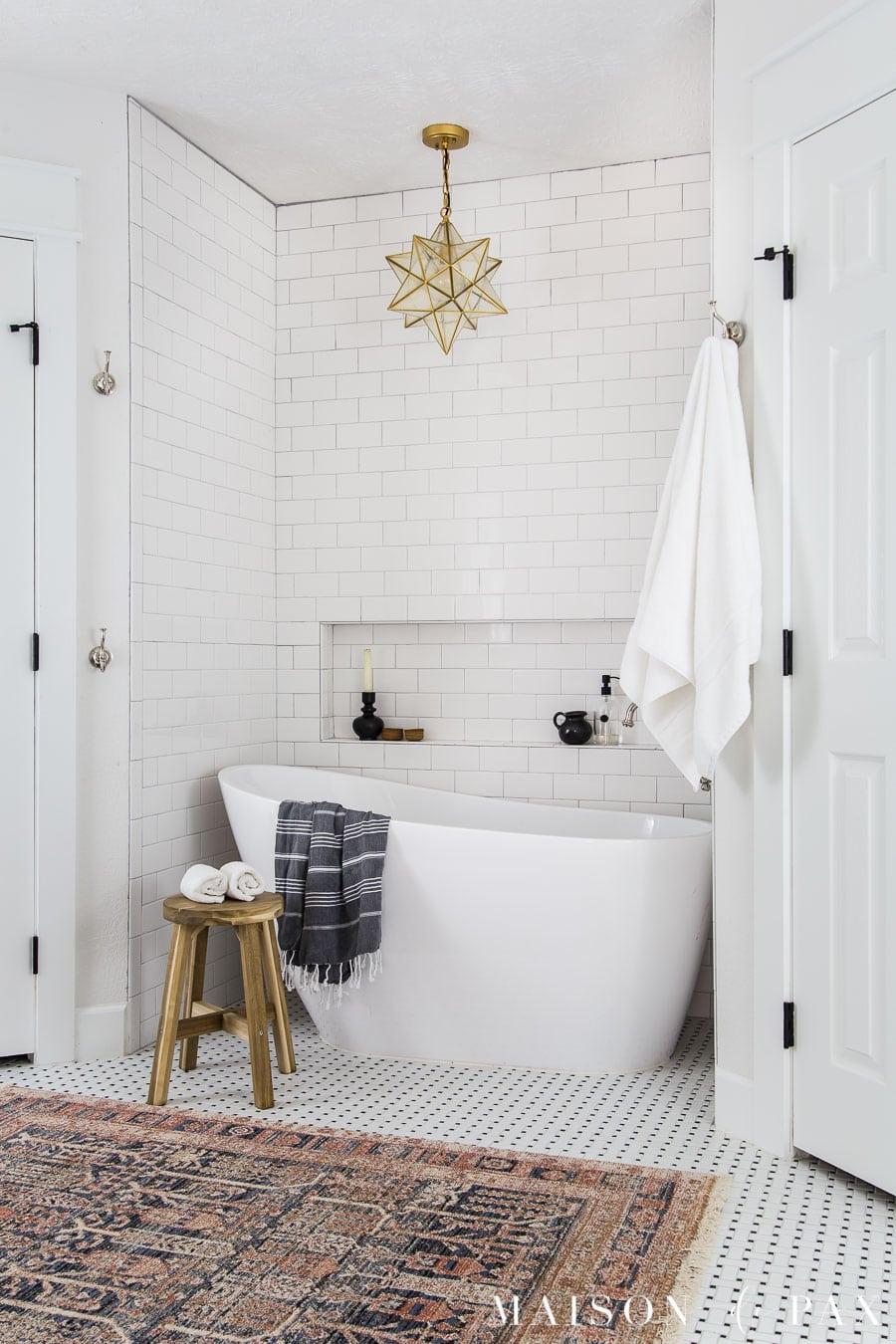 freestanding slipper tub in tiled nook with white subway tile
