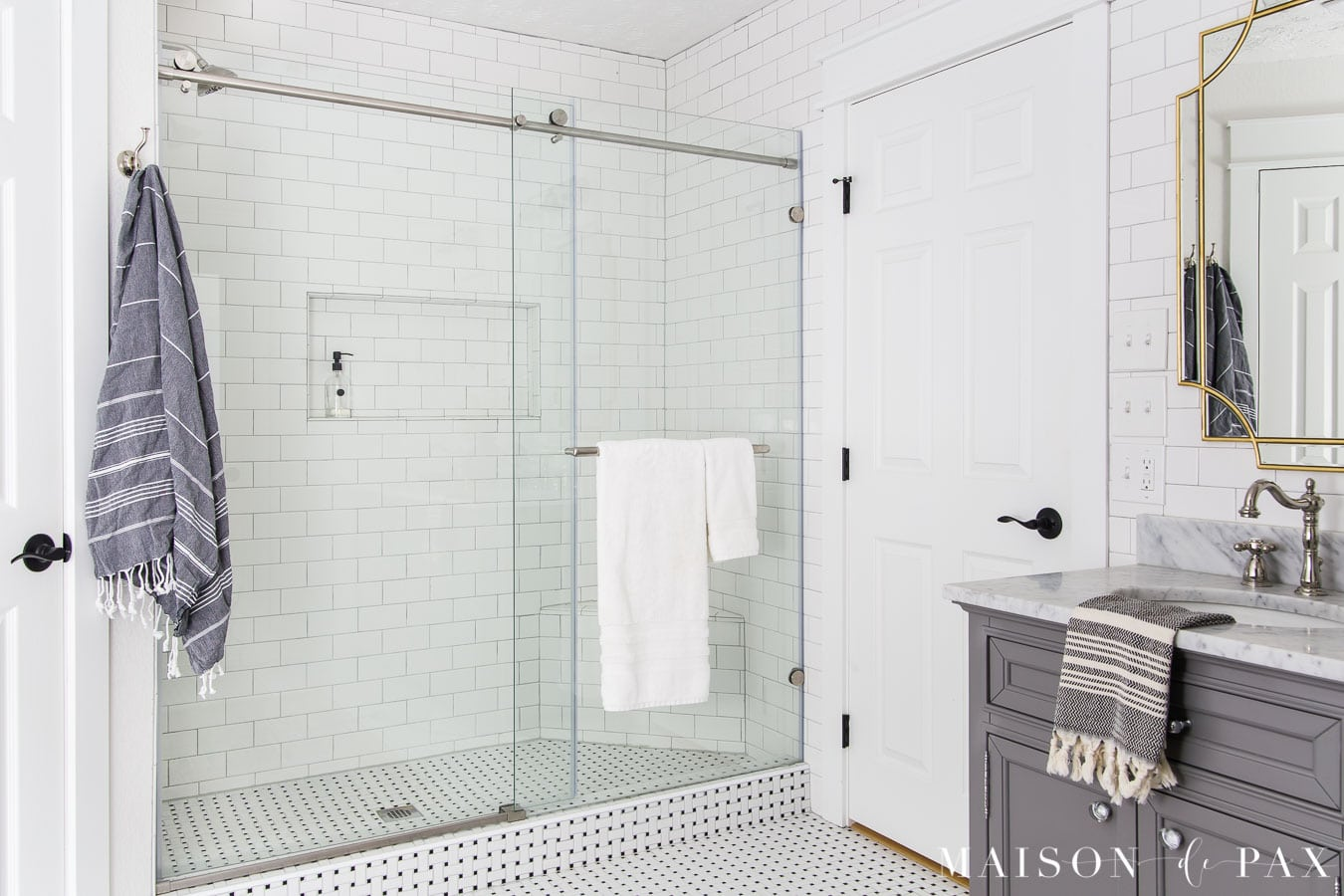 walk in shower with black and white basketweave tile floors